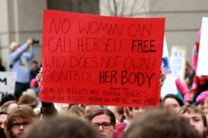 """Sign at Women's March reads, """" No woman can call herself free who does not own control her body. Women's rights are human rights. Human rights means we are all more free!"""""""