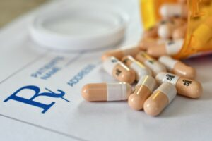 Pills spilling from bottle onto prescription pad
