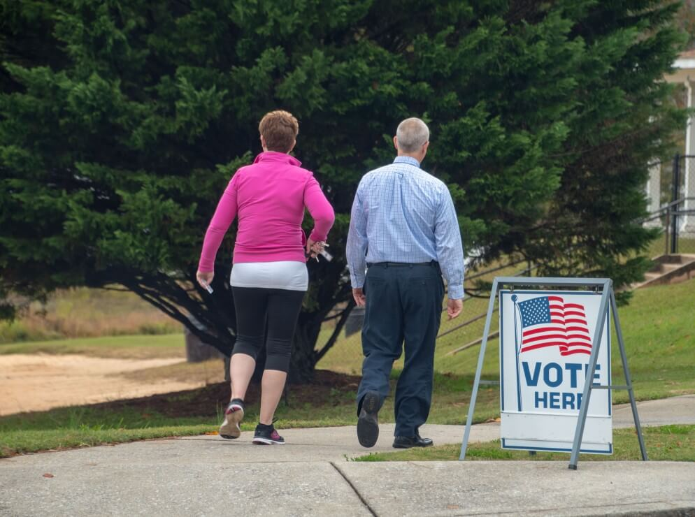 "Two white people walk by ""vote"" sign at polling location"