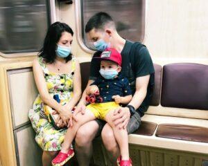 Family wearing masks rides public transportation