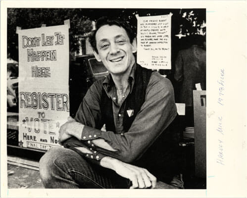 """Harvey milk sitting in front of castro camera on castro street, san francisco  1977 sign reads, """"don't let it happen here"""" - register to vote"""""""
