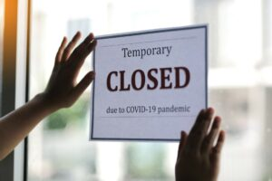 """Sign on window reads, """"Temporarily closed due to COVID-19 pandemic."""""""