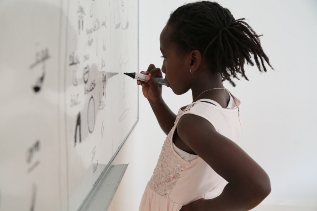 Young black student writing on white board in school