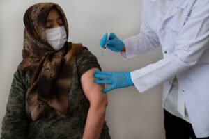 An elderly woman wearing a mask and a hijab receives the coronavirus vaccine
