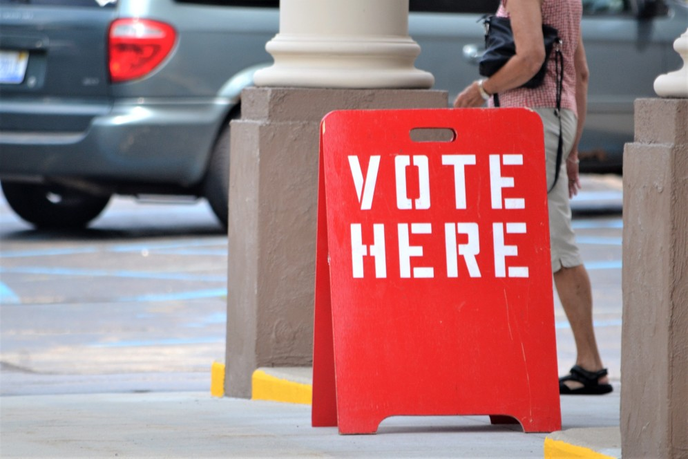 "Red ""Vote Here"" sandwich board sign"