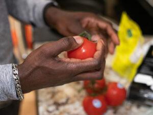 Black man holds tomato