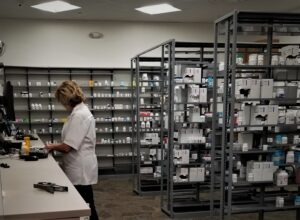 Pharmacist working in back of pharmacy; shelves with medicine