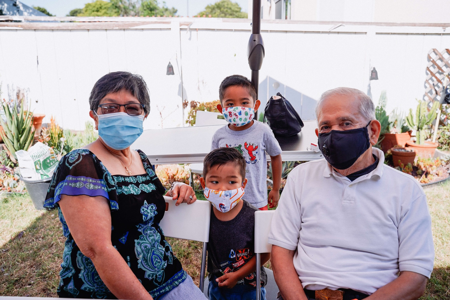 Generational family sitting outdoors wearing protective masks
