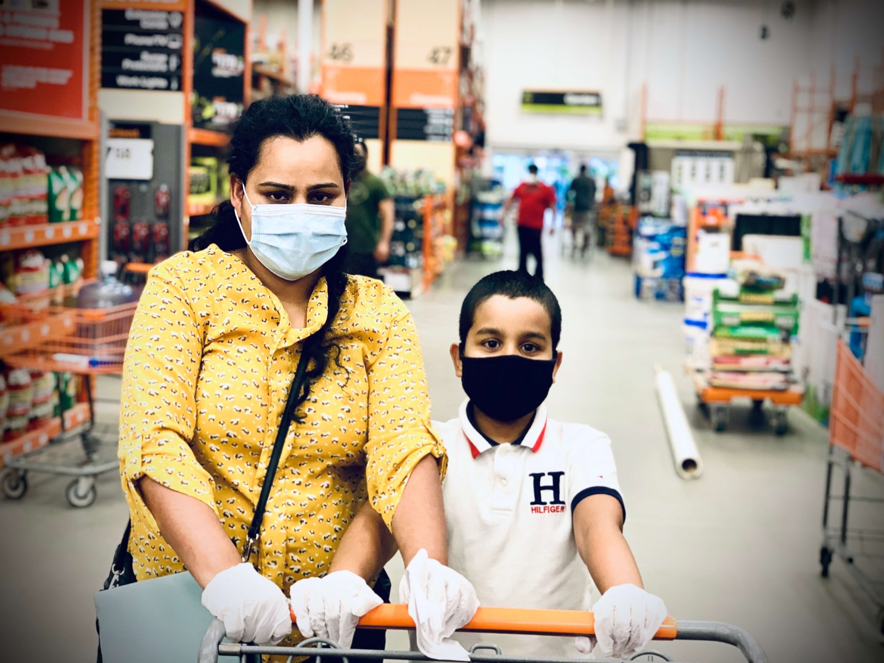 Mother and child pushing a cart through a grocery store while wearing protective masks