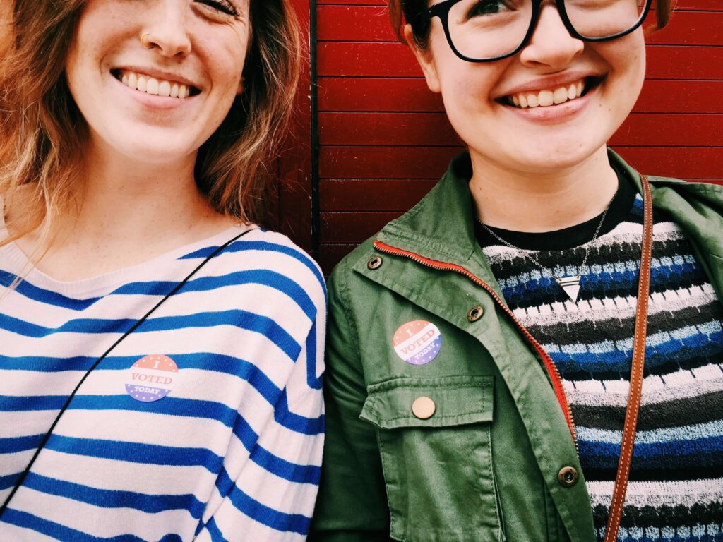Two happy young women wearing i voted stickers