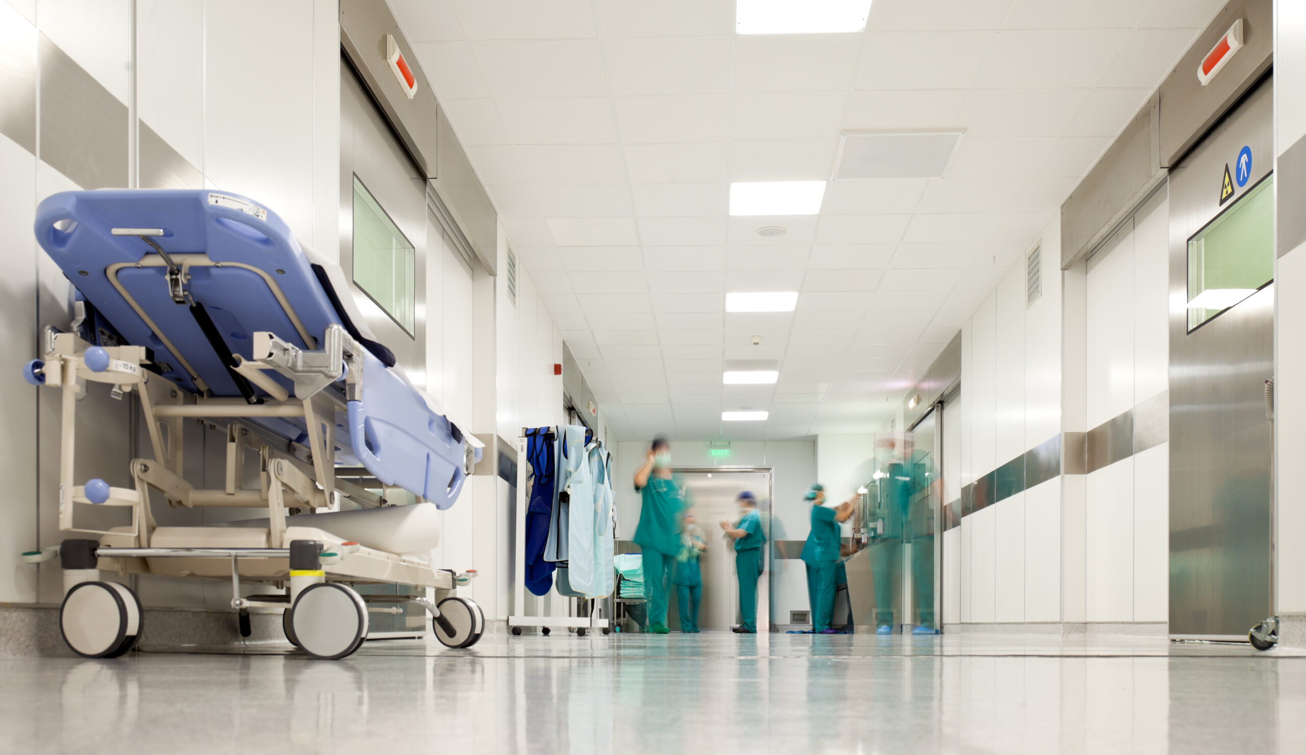 People with medical uniforms in hospital corridor