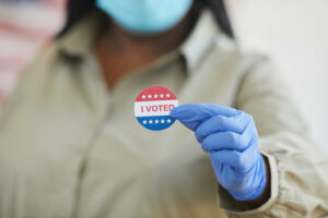 """Masked and gloved person holding """"I Voted"""" sticker"""