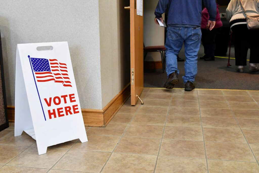 """""""vote here"""" sign inside polling place; people queued to vote"""