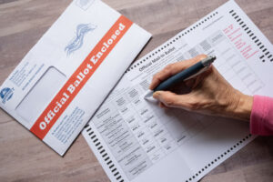 """Person filling out absentee mail ballot for election. Envelope reads """"Official Ballot Enclosed"""""""