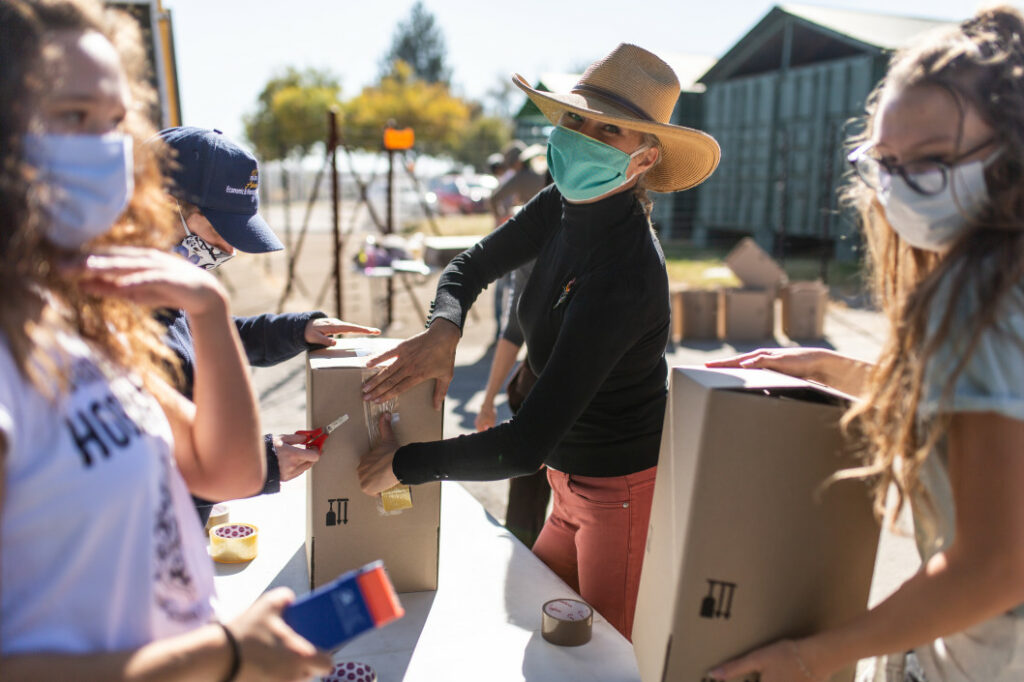 Masked women packing food