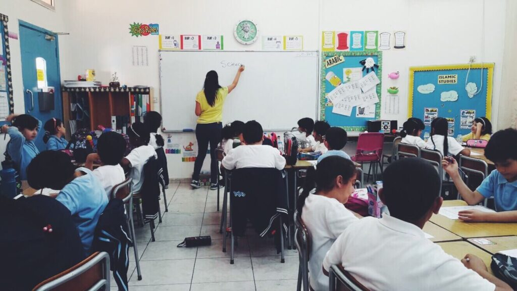 Teacher writing on white board in front of their class