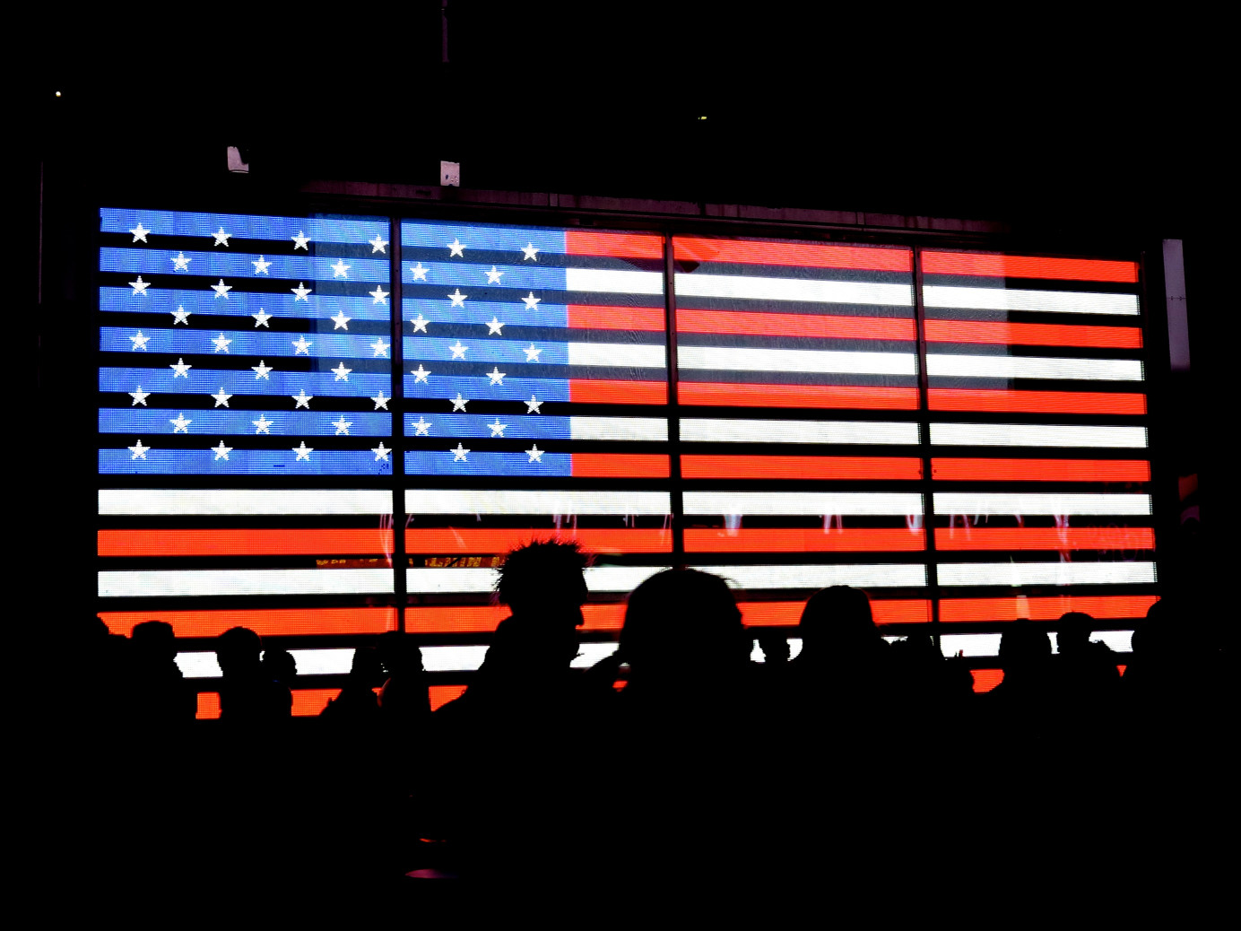 Silhouette of people in front of neon American flag