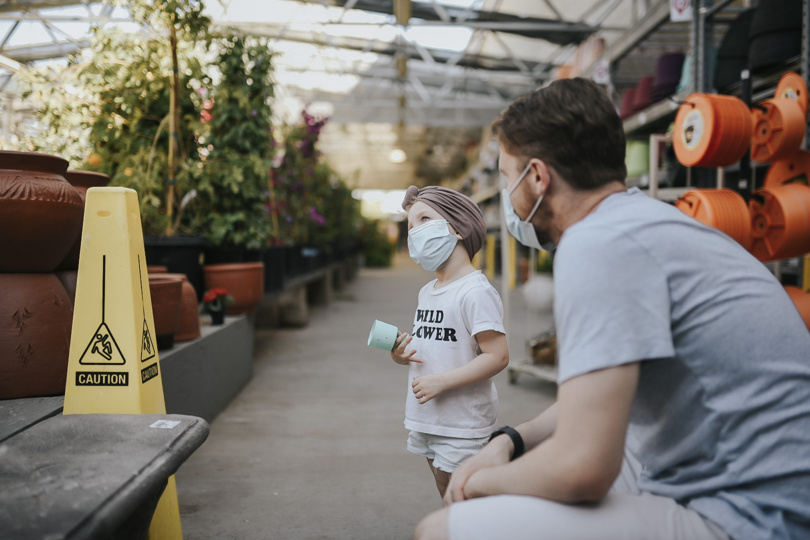Parent and child with masks in garden store
