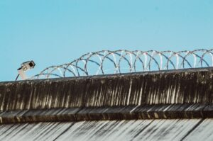 Security camera on fence with barbed wire