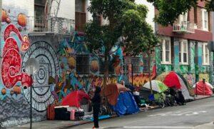 Tents alongside a mural in San Francisco