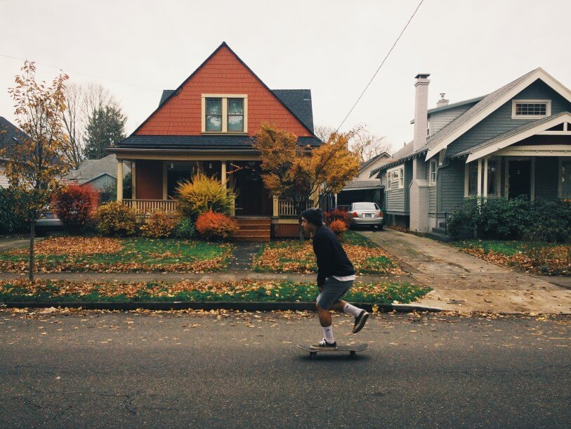 A young man skateboards past an old house in portland, oregon