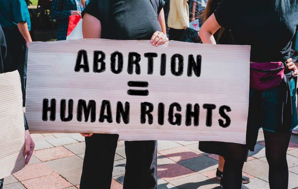 """Protest sign reads, """"abortion = human rights"""""""