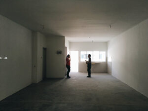 Two people stand in empty house or apartment