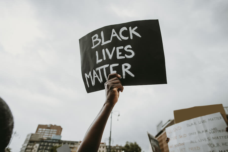 "Holding sign that reads, ""Black Lives Matter"""