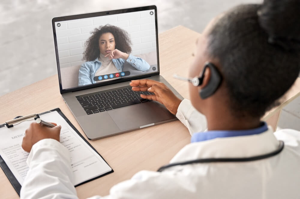 Black doctor meets with patient virtually for telehealth appointment
