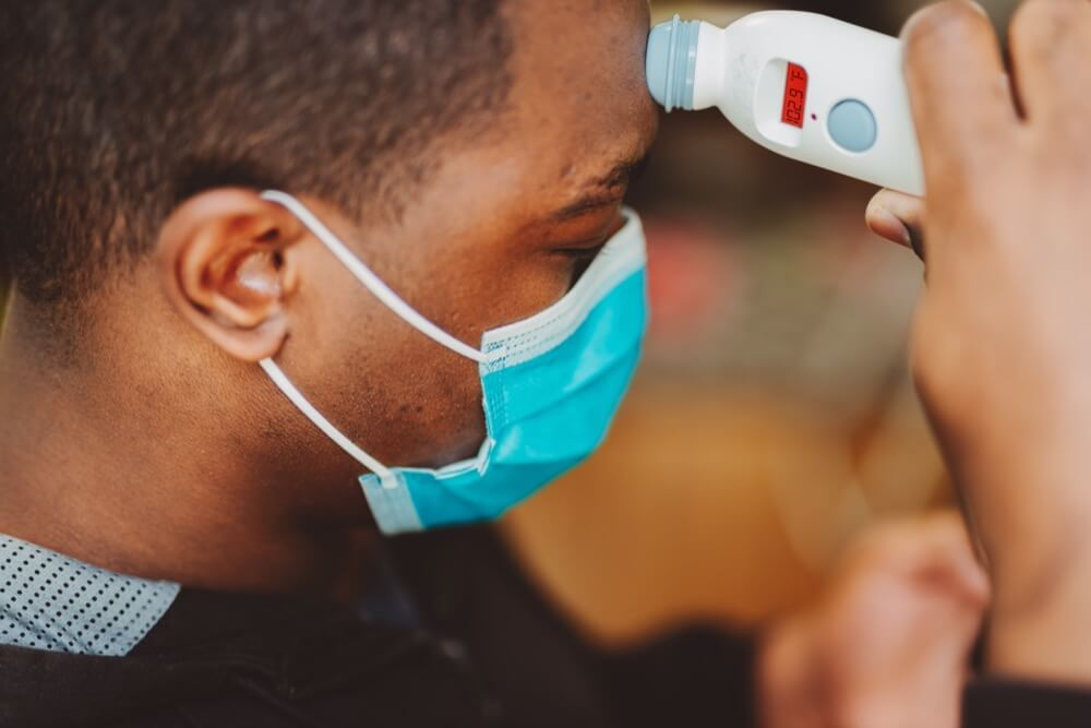 Black man in surgical mask takes his temperature
