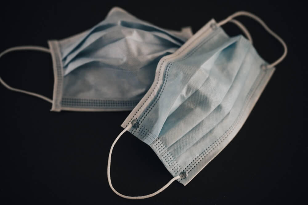Two blue surgical masks on black surface