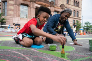 Black father and son painting mural on ground.