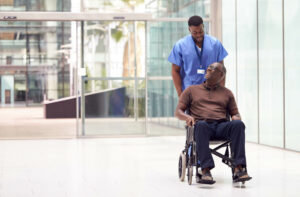 Black healthcare professional rolling patient in wheelchair