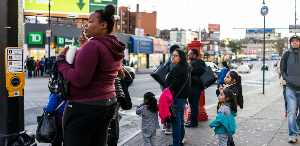 Black and brown families wait to cross the street at the light in the bronx, new york
