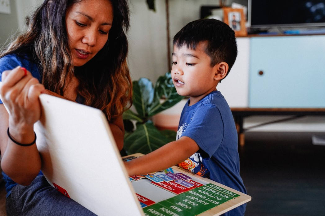 Asian toddler playing on laptop with mother