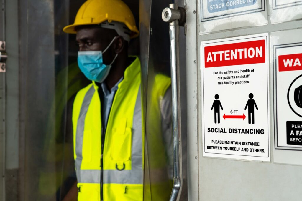 Black construction worker wearing mask and vest. Sign on wall advises about covid-19 and social distancing.