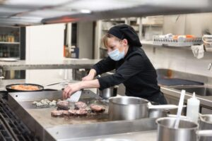 Chef or cook wearing a mask and cooking in an industrial kitchen