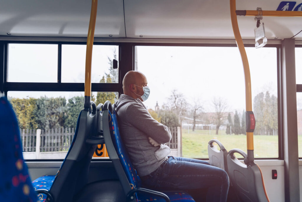 Man wearing protective mask sits on bus during the day