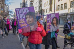 Demonstrators carry signs thanking stacey abrams and andrea miller at a manhattan rally in support of the equal rights amendment.