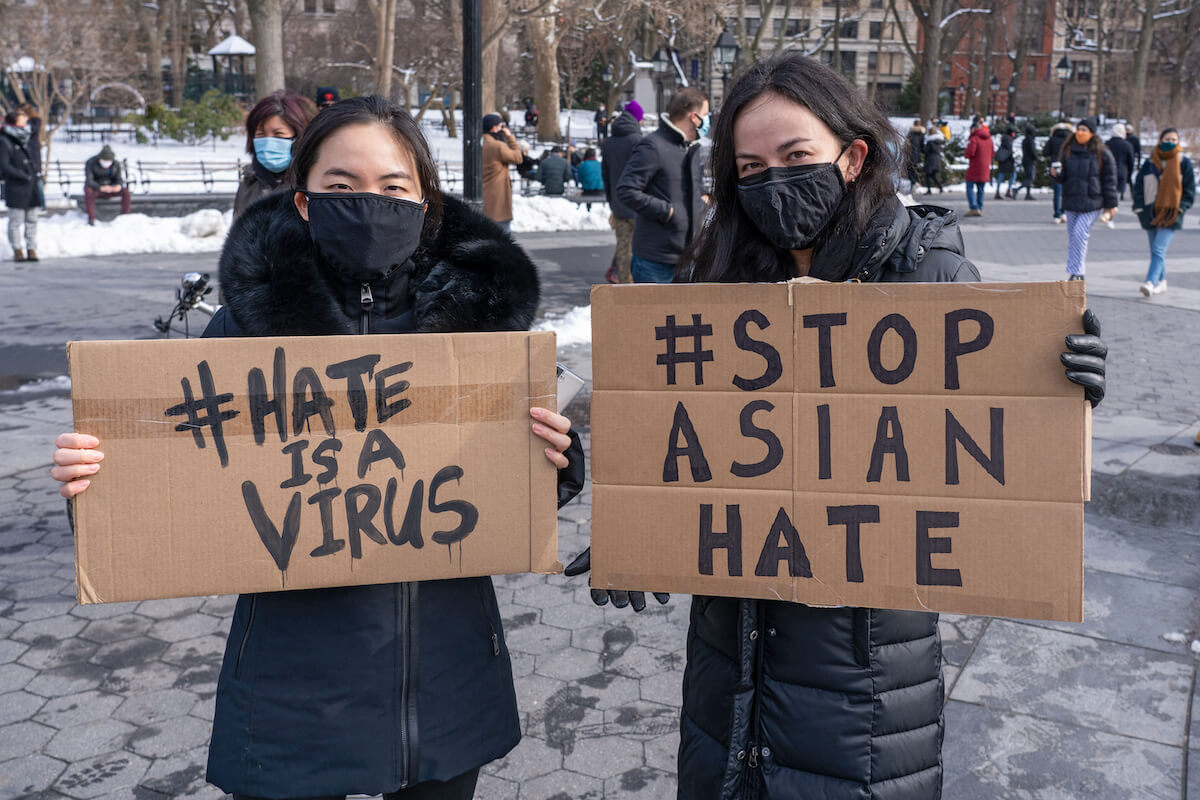 """Protestors in new york city hold signs reading """"hate is a virus"""" and """"stop asian hate"""""""