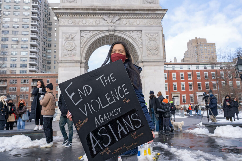 "Demonstrator at a rally holds sign that reads, ""end the violence against asians"""