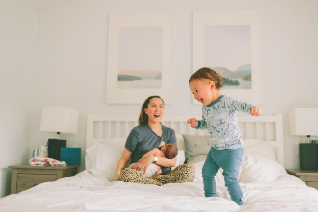 Mother nursing baby while toddler jumps on bed