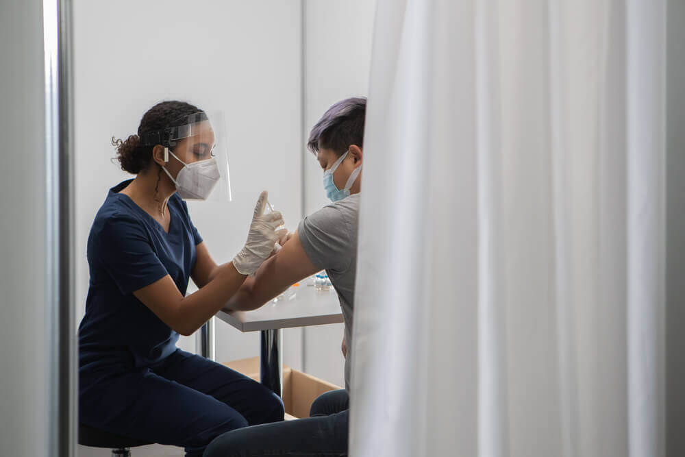 Black woman doctor prepares to administer vaccine to an asian patient in vaccination cabin