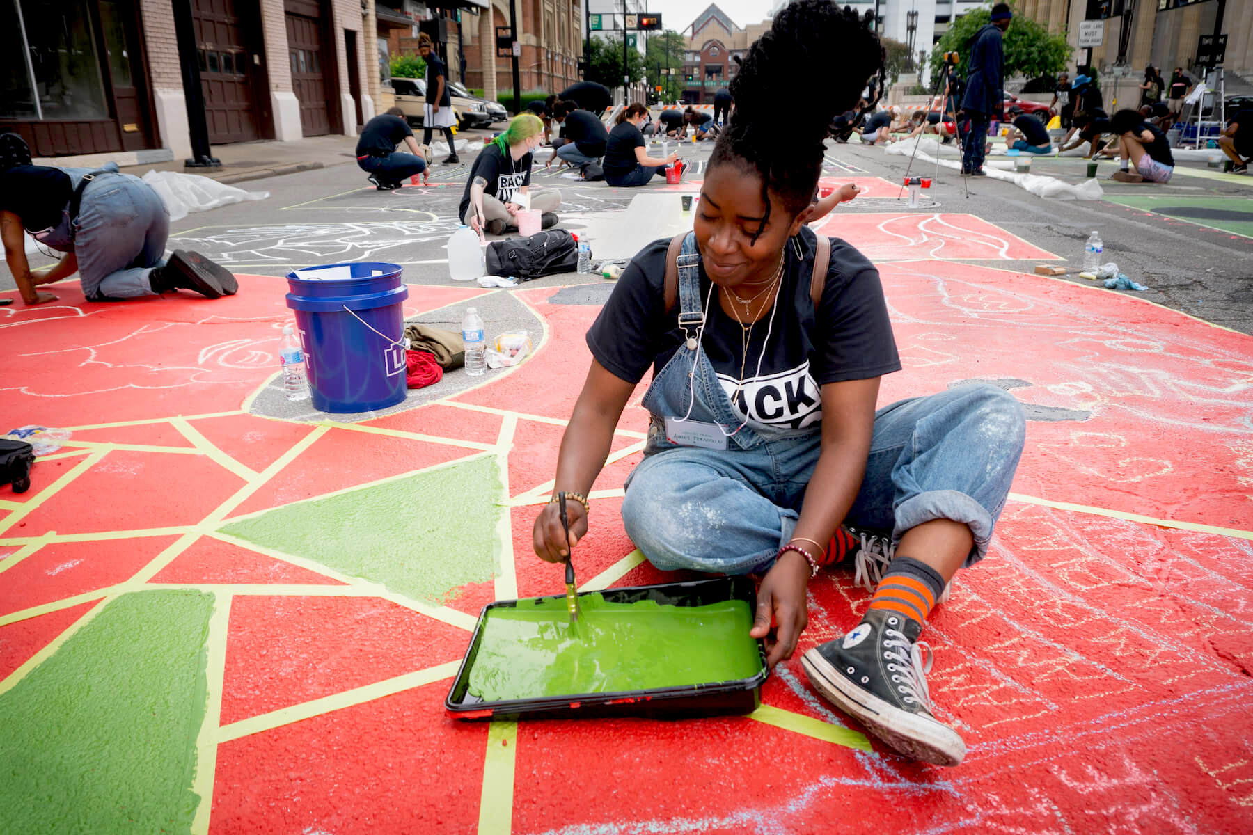Mural artists collectively create street art in front of city hall