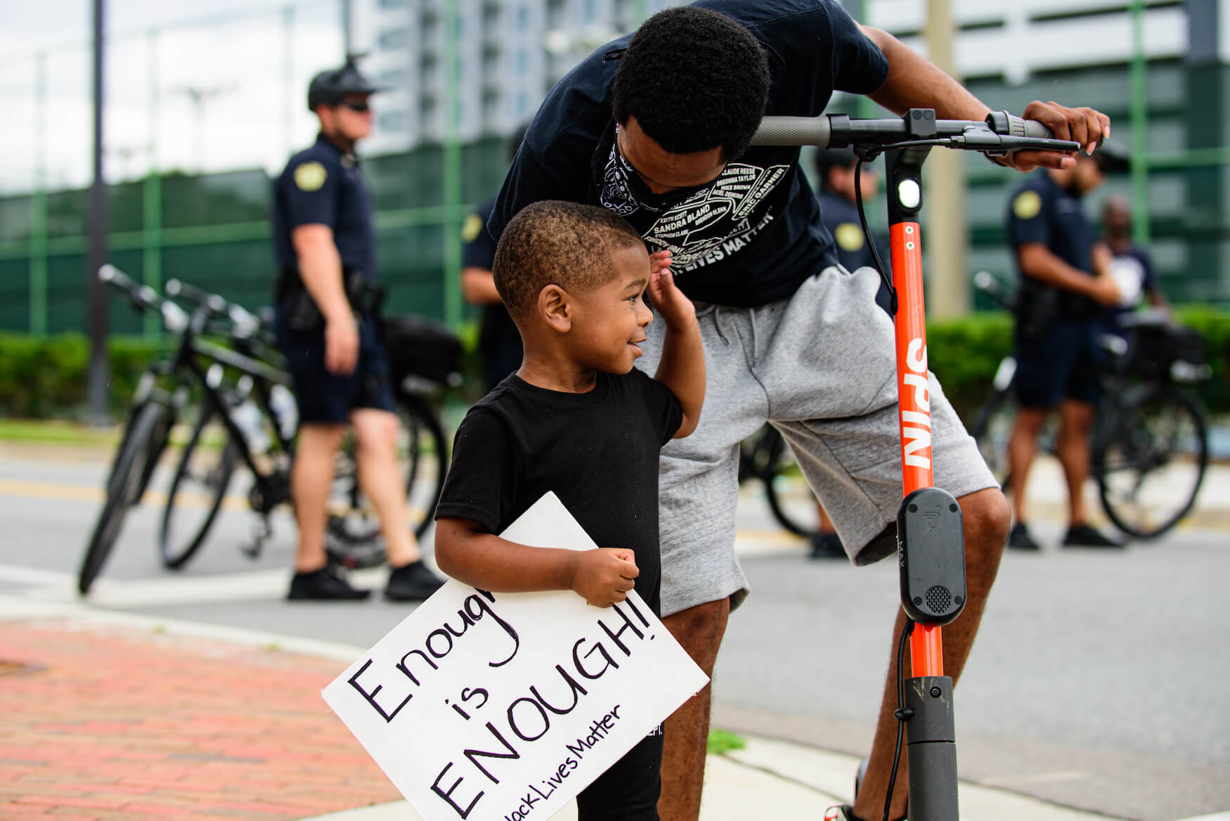 """Black father and son at black lives matter demonstration with sign reading """"enough is enough"""""""