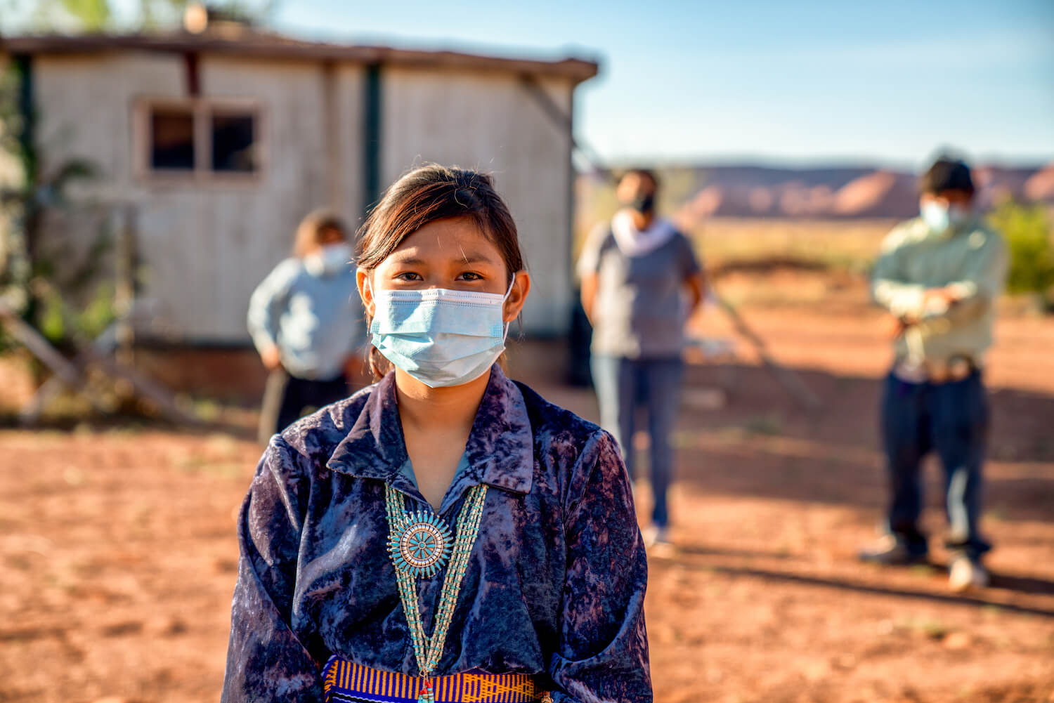 Navajo family social distancing with covid masks outside their home in monument valley arizona