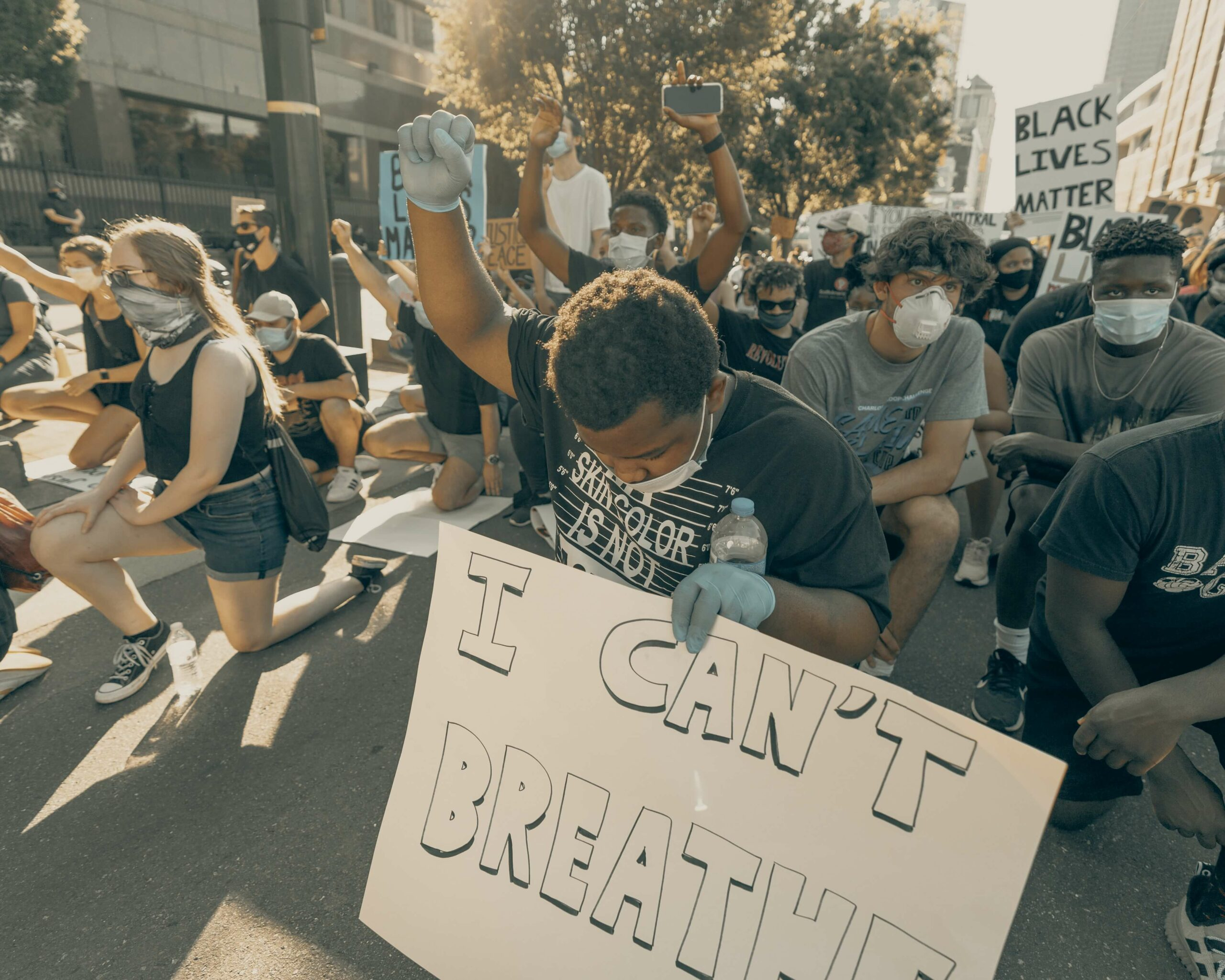 Protestor holding up his fist in solidarity; photo by clay banks