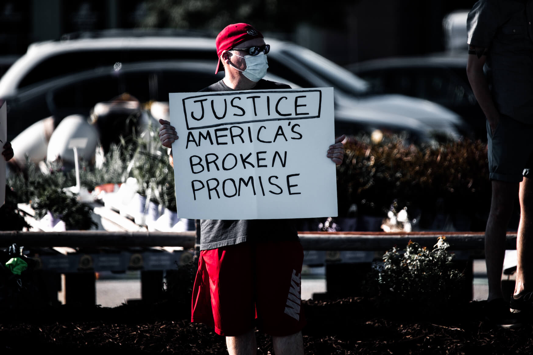 """Protester in omaha, nebraska protests the killing of george floyd; sign reads """"justice: america's broken promise"""""""