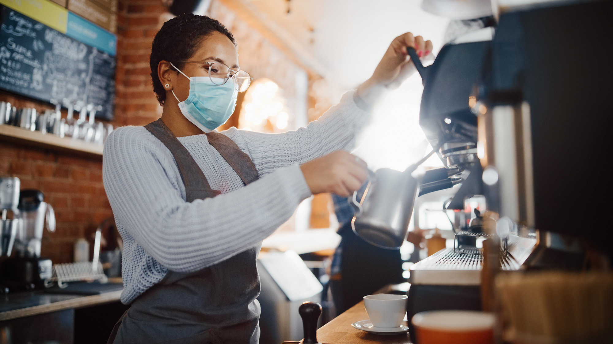 Barista wearing mask making latte in coffee shop