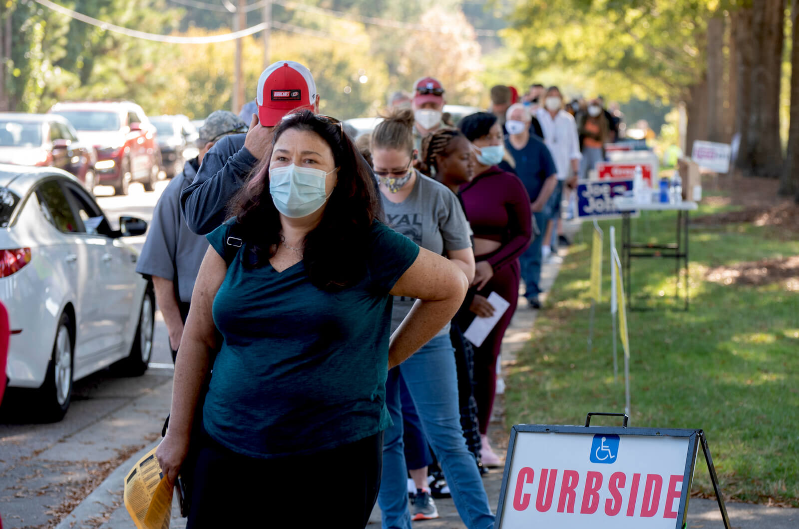 A lady wearing a face mask is amongst a diverse group of voters on the first day of early voting.